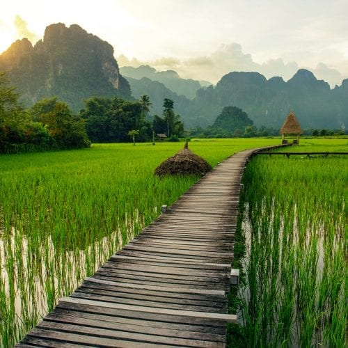 Sunset over green rice fields and mountains in Vang Vieng, Laos
